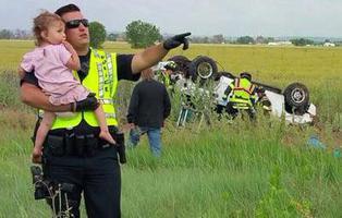 Un policía consuela a una niña después de perder a su padre en un accidente de tráfico