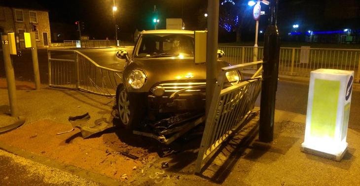 El coche se llevó por delante las vallas de la calle