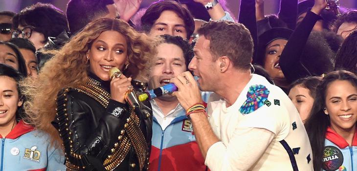Dudamel, entre Beyoncé y Chris Martin, rodeaado por los miembros de su orquesta juvenil