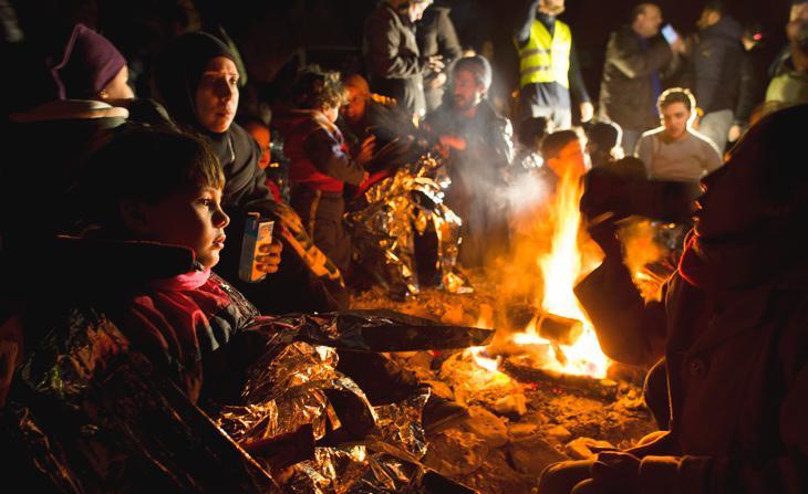 Niños pequeños se calientan junto a hogueras en el campamento de refugiados de Lesbos