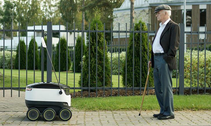 Uno de los robots repartidores ante un anciano