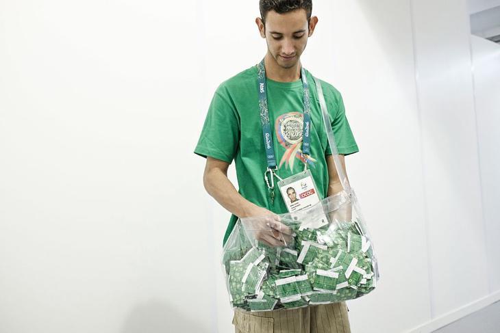 Un voluntario de Río 2016 entregando condones