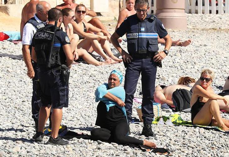 Los policías hablan con una mujer con burkini