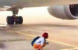 Una mujer se sienta debajo de un avión para impedir que despegue el vuelo que había perdido