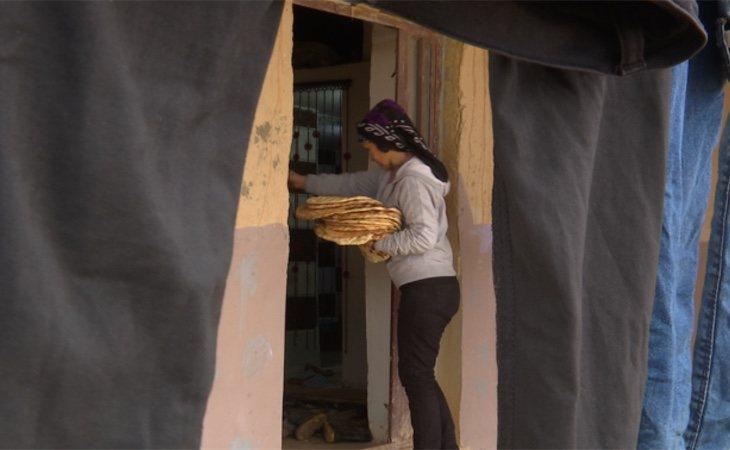 Zeinab con el pan que venden para mantenerse económicamente