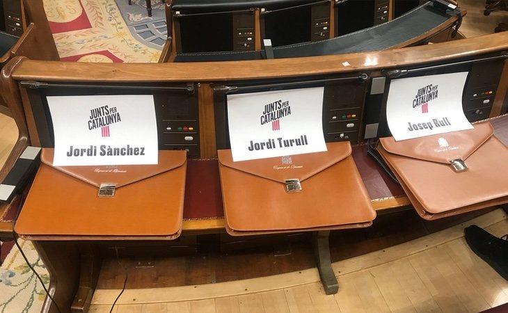 Los diputados de Junts per Catalunya colocan los nombres de los diputados presos sobre sus carteras para mostrar su ausencia en el pleno