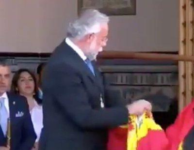 Acusan a un alcalde del PP de limpiarse una caca de paloma con la bandera de España