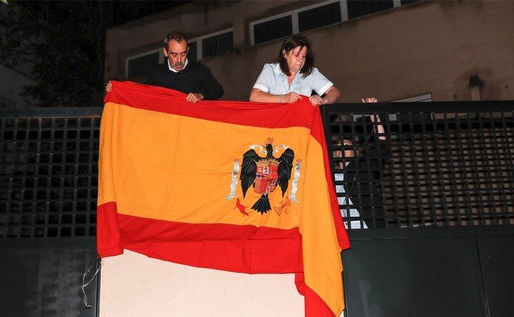 La empleada del hogar de Francis Franco, nieto del dictador, cuelga una bandera preconstitucional en la fachada de su vivienda