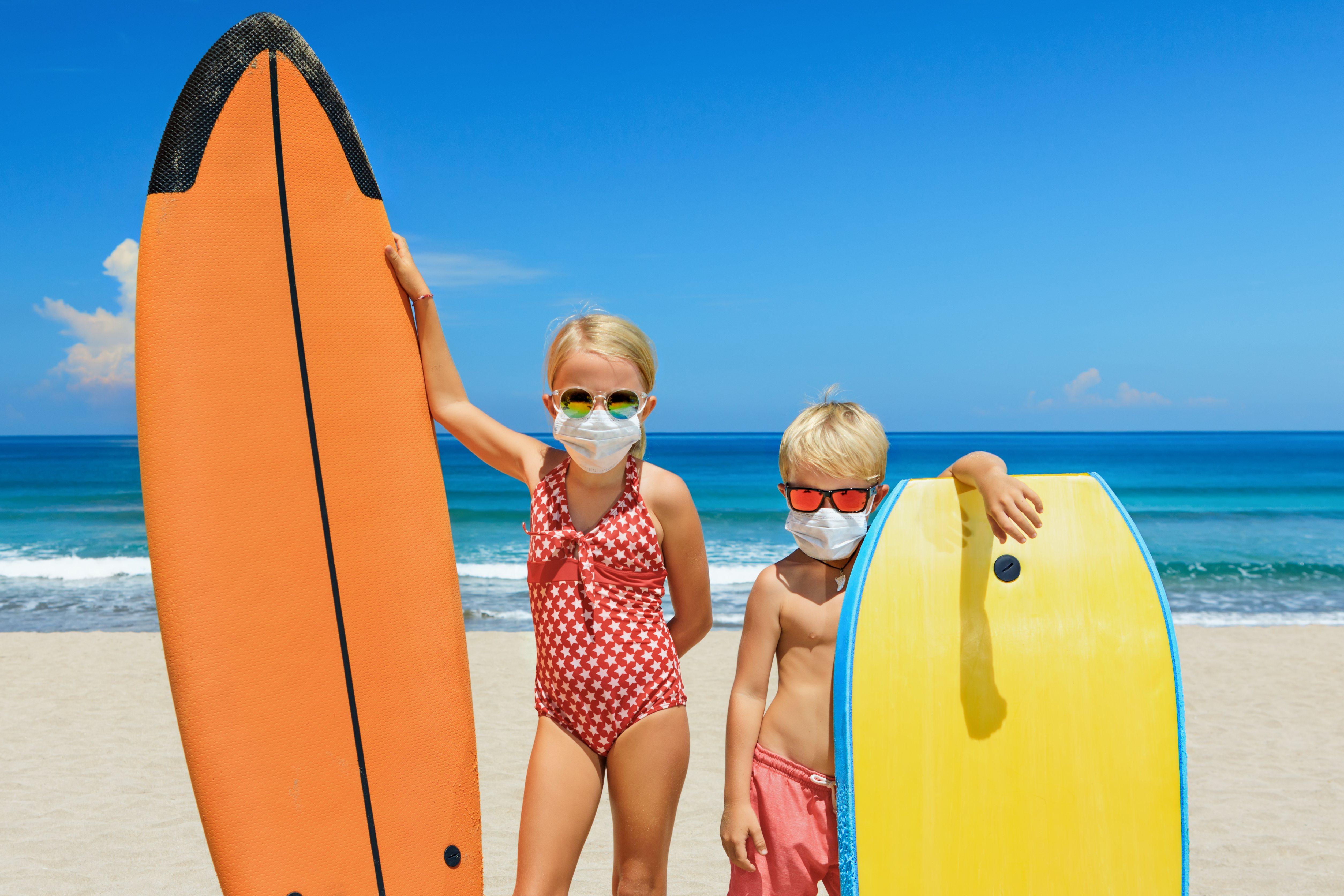 Jóvenes surfistas con tablas de surf usan máscaras protectoras en la playa.