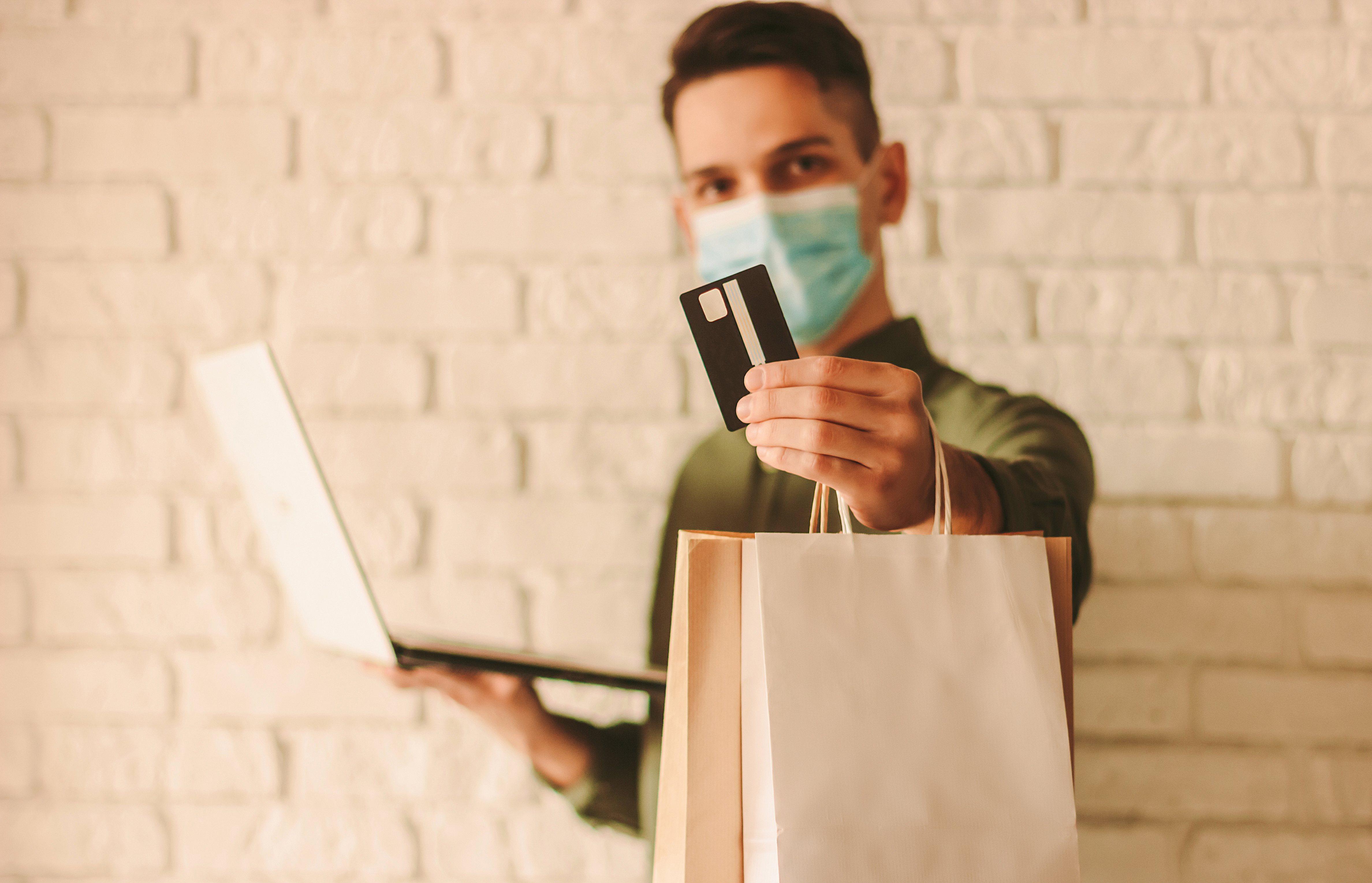 Hombre feliz con la máscara protectora haciendo compras en la tienda de internet.