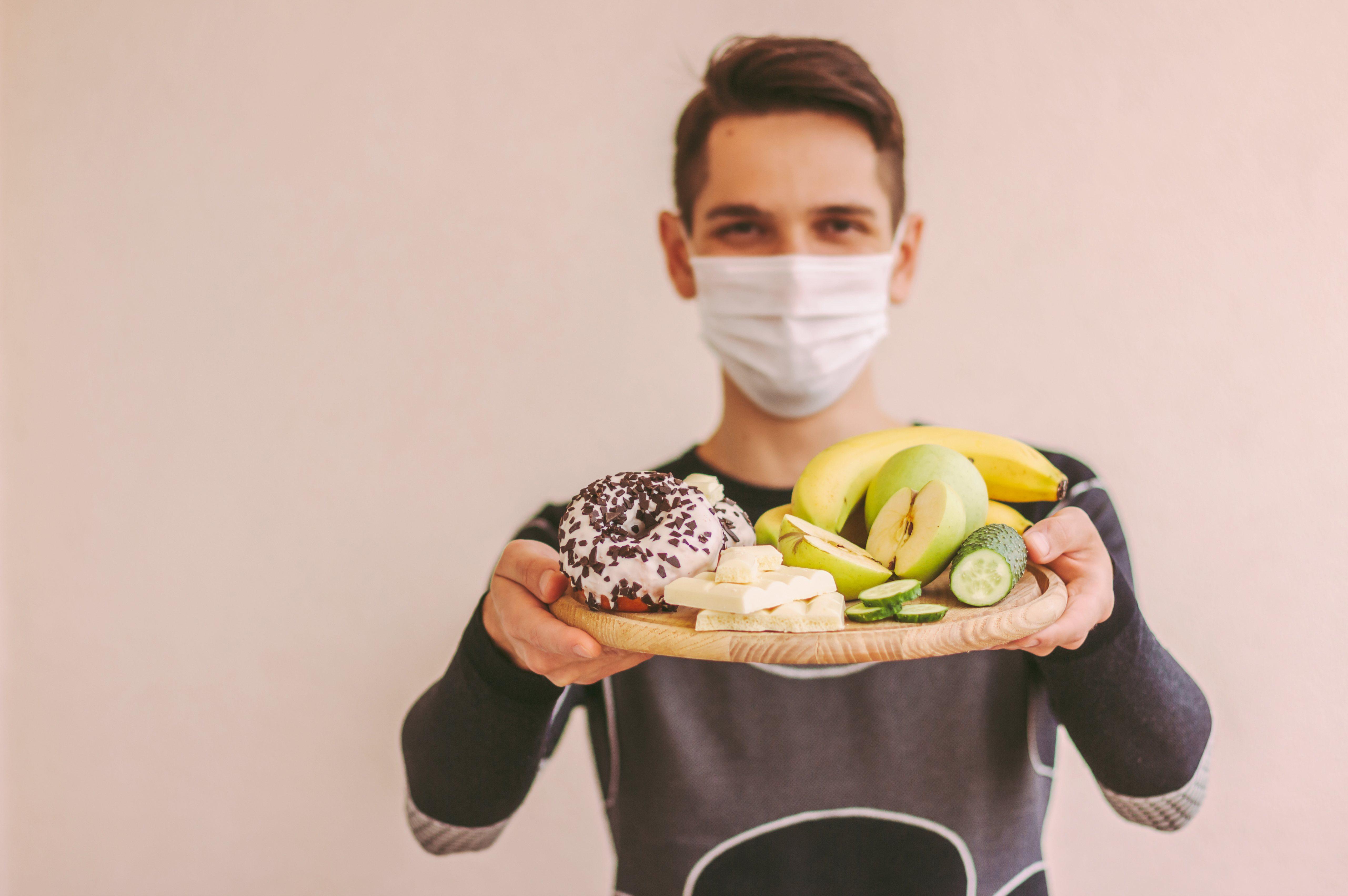 Feliz deportista con mascarilla médica sosteniendo tablón de madera con verduras, frutas frescas, donut y chocolate.