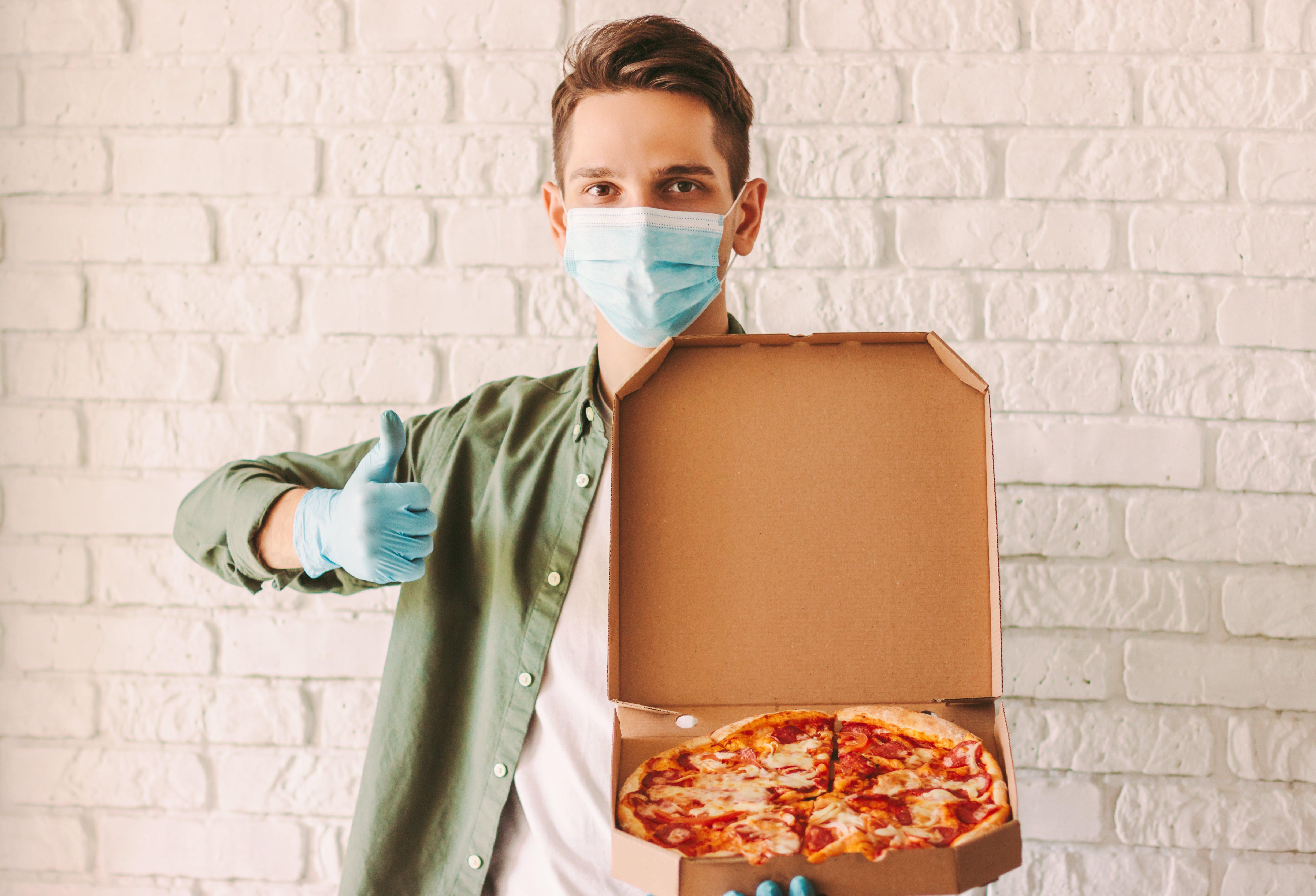 El trabajador del servicio de entrega de pizza de un hombre hipster con mascarilla médica y guantes sostienen una caja de cartón en la mano y muestran gesto de pulgar arriba.