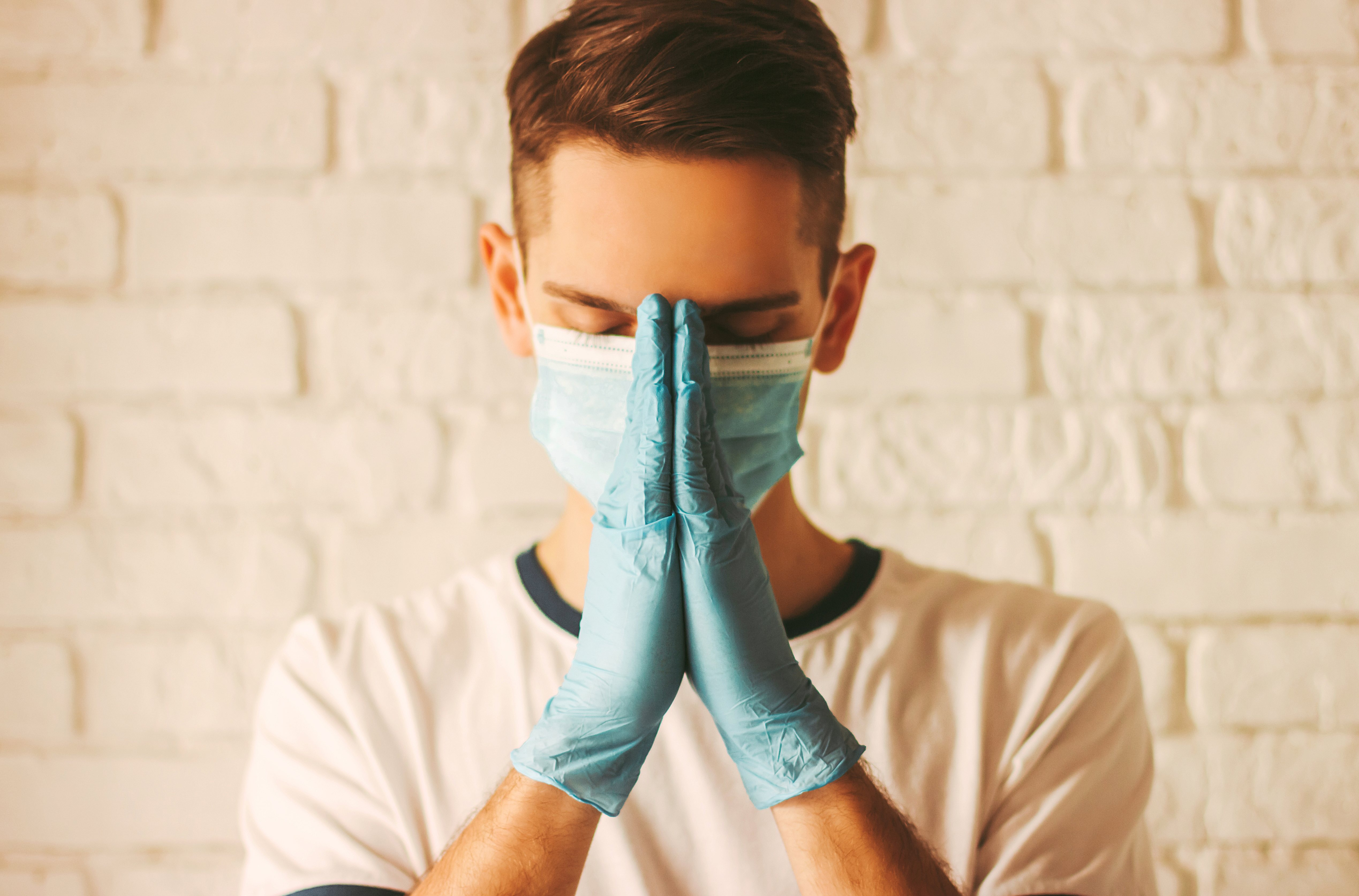 Joven doctor reza con mascarilla y guantes en un hospital