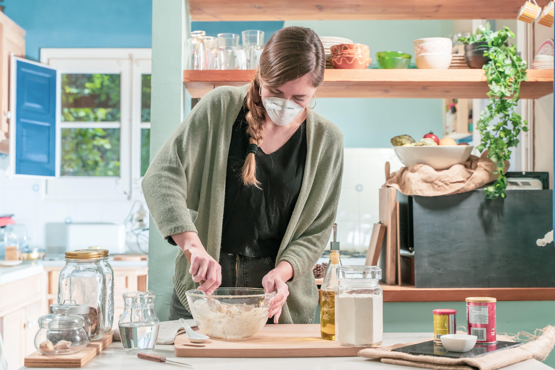 Mujer guapa aislada con mascarilla en cuarentena cocina en casa durante la crisis del coronavirus. Preciosa cocina rústica
