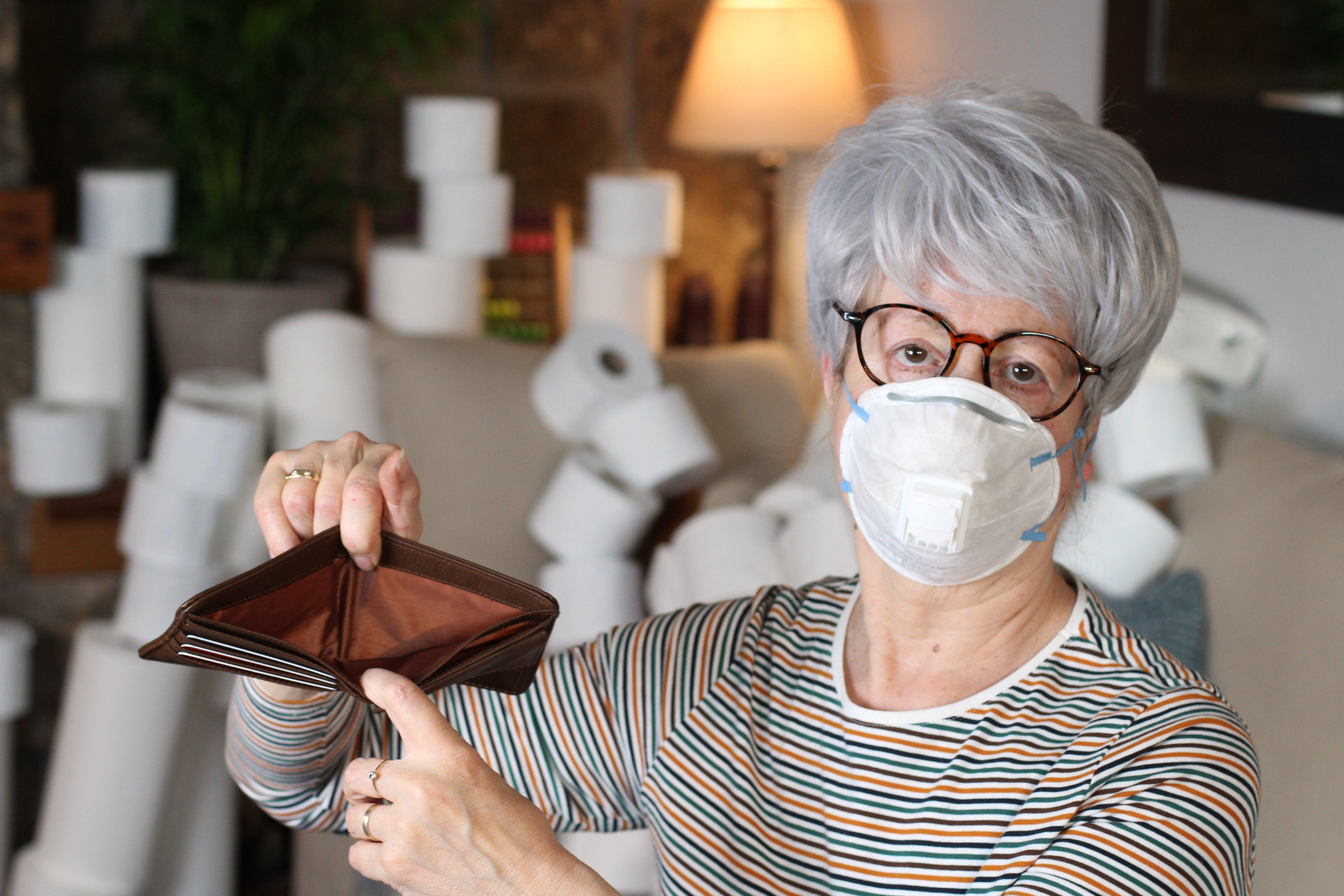 Anciana enferma sujetando una cartera vacía