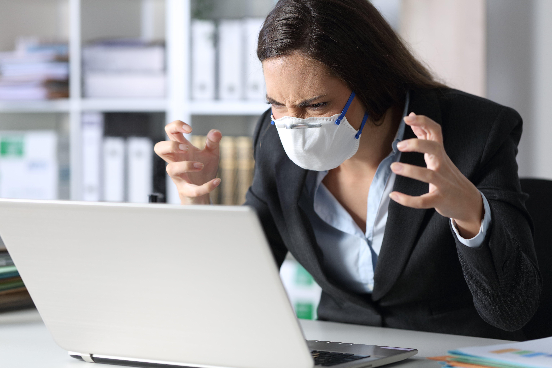 Mujer ejecutiva furiosa leyendo malas noticias en una laptop evitando covid-19 con máscara en un escritorio en la oficina