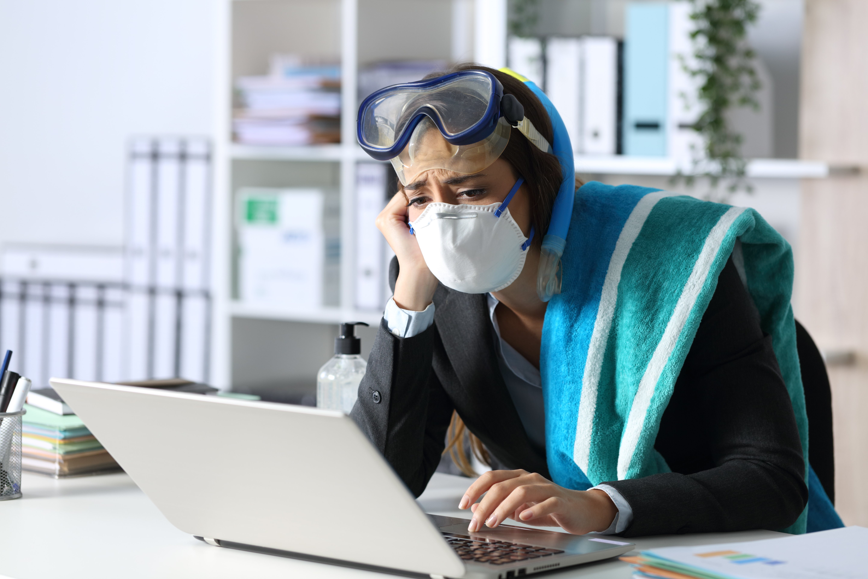 Triste mujer ejecutiva con máscaras cancelando vacaciones en una laptop en la oficina usando gafas y toalla