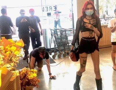 Una dominatrix pasea por un hombre con correa y careta de perro por un supermercado