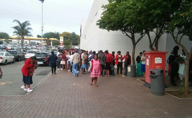 Una larga cola se forma fuera de un comercio en Sudáfrica (Penwell Dlamini)