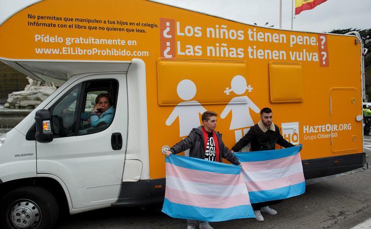 Dos activistas ante la caravana transfóbica de Hazte Oír