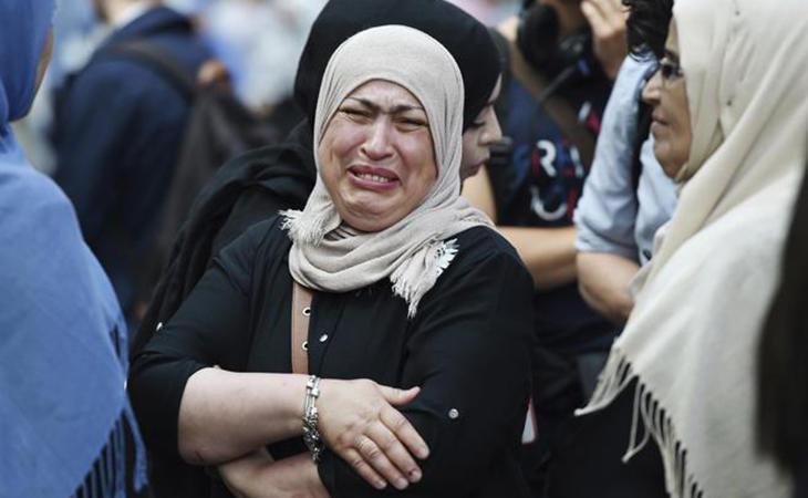 Una mujer llora al ver su casa quemada