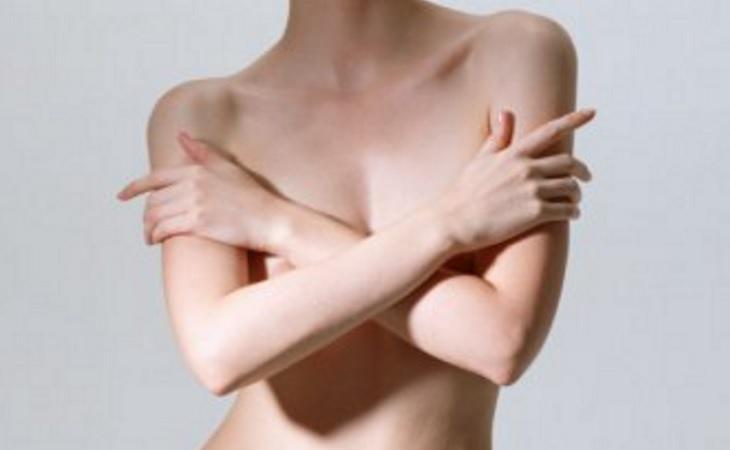 Una persona desnuda tapando parte de su cuerpo con sus brazos