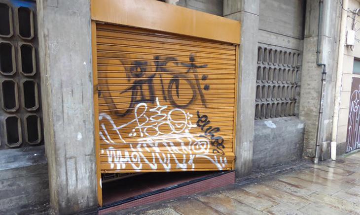 La puerta del garaje de la residencia tras ser golpeada por los jóvenes