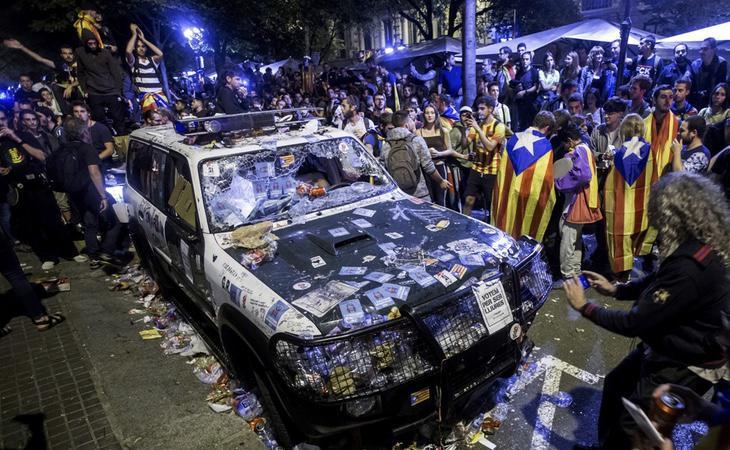 Manifestantes 'pacíficos' destrozan un coche de la Guardia Civil mientras intentan evitar su trabajo