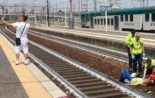 Un chico se hace un selfie con el símbolo de 'victoria' ante una mujer arrollada por un tren