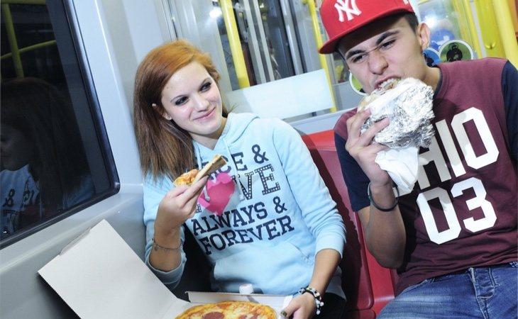 Jóvenes comiendo pizza en el metro