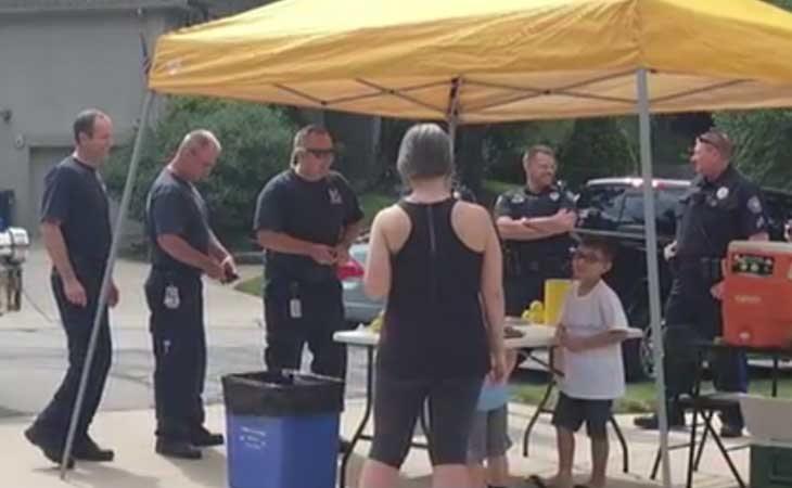 Los agentes de policía ayudante a montar de nuevo el puesto de venta de limonada