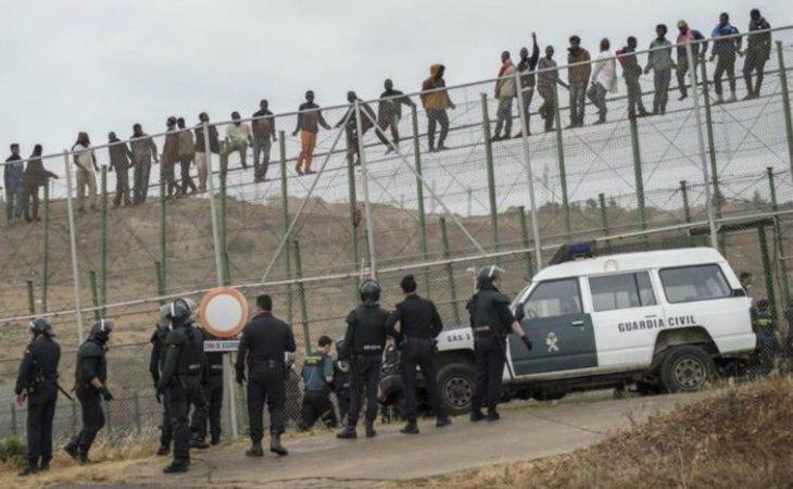 Migrantes en la valla de Melilla ante el cordón de la Guardia Civil