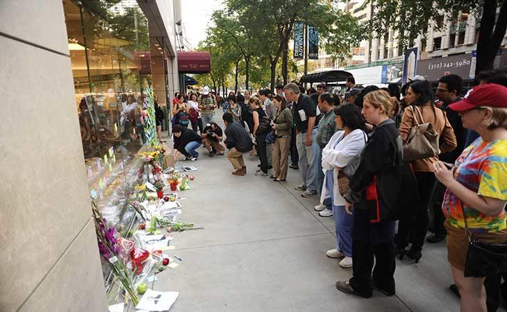 Personas colocando ramos en una tienda de Apple tras la muerte Jobs