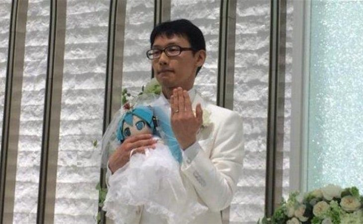 Akihiko posa con Hatsune mostrando las alianzas durante la ceremonia