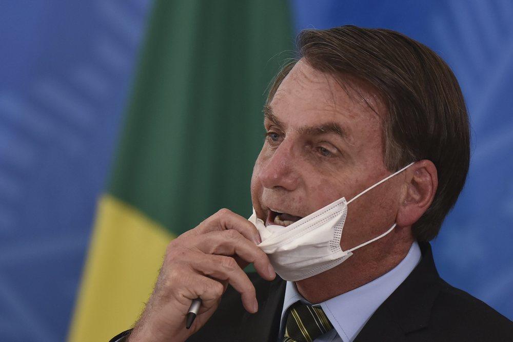 Bolsonaro se coloca una mascarilla protectora para dar una rueda de prensa