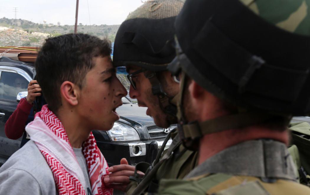 Un joven palestino grita a un solado israelí en el Día de la Tierra Palestina