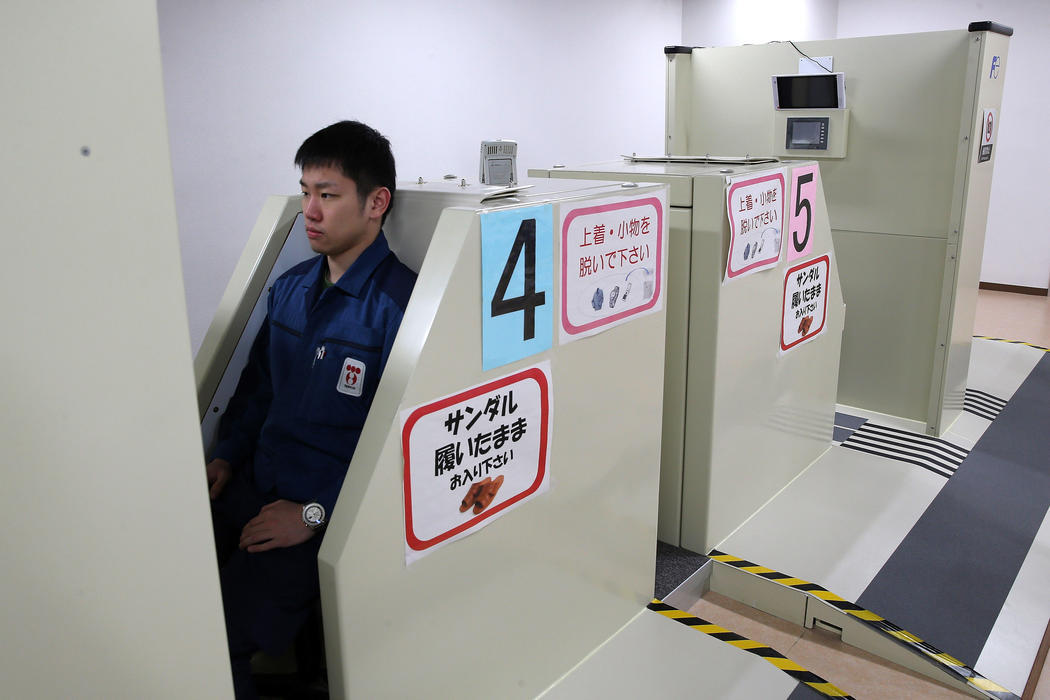 Un trabajador pasa por el escáner de radiación al terminar su jornada laboral