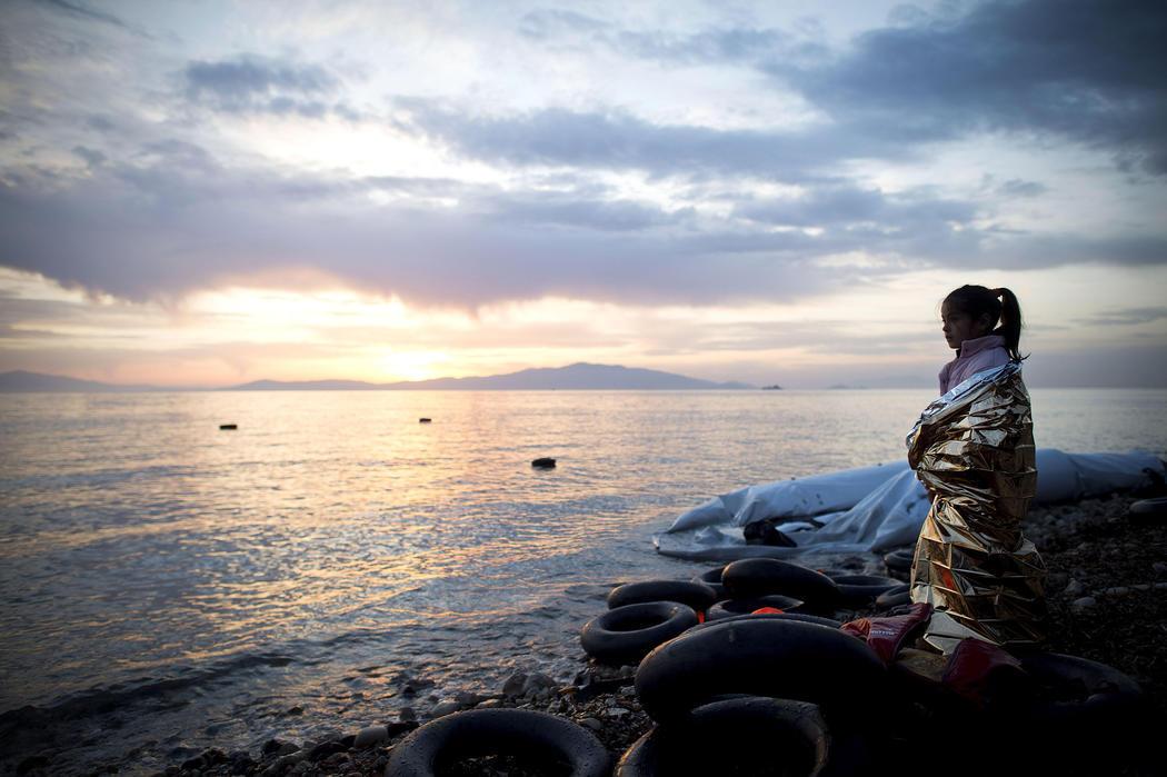 Una niña siria se abriga con una manta térmica