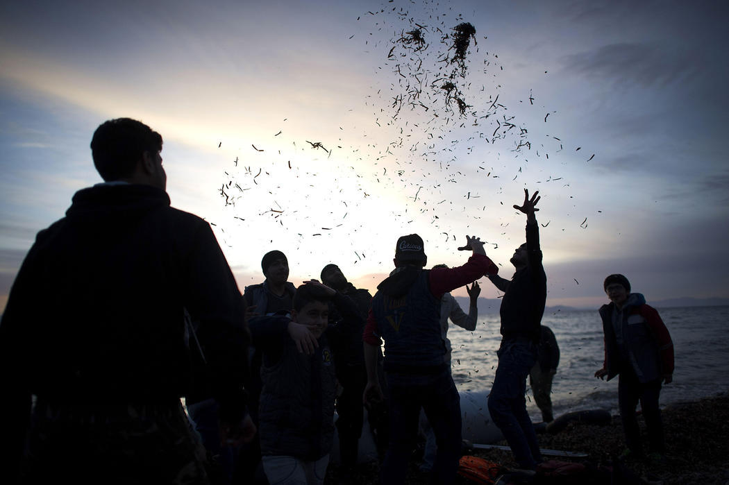 Un grupo de refugiados celebra su llegada a la costa