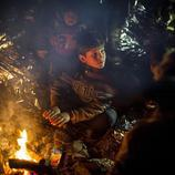 Niños y adultos se reúnen alrededor de una hoguera