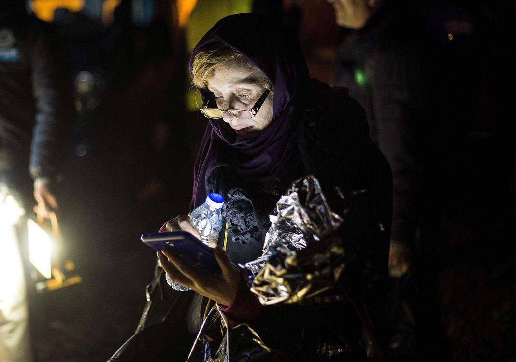 Una mujer afgana consulta su teléfono tras ser rescatada