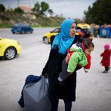 Una madre carga con su hijo y algunas pertenencias