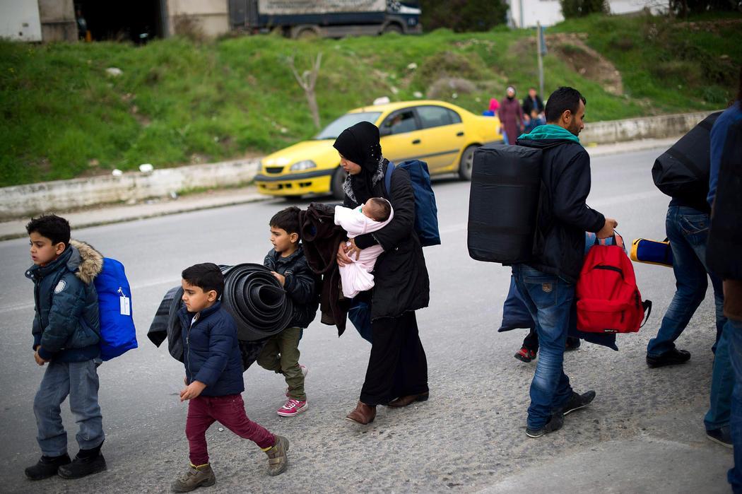 Una madre cuida de sus cuatro hijos tras su llegada a la costa griega