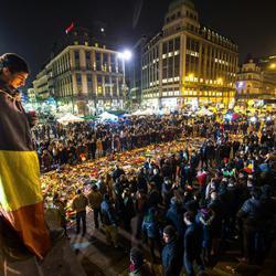 Un joven envuelto en la bandera belga deja una vela en el memorial de Bruselas
