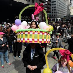 Un padre lleva a hombros a su hija disfrazada de cesta de Pascua