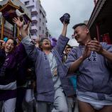 Un grupo de personas cantan y bailan alrededor del mikoshi