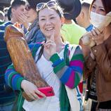 Una mujer posa con un falo gigante tallado en madera