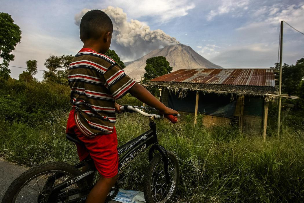 Un niño de Kuta Tengah observa la erupción del volcán Sinabung