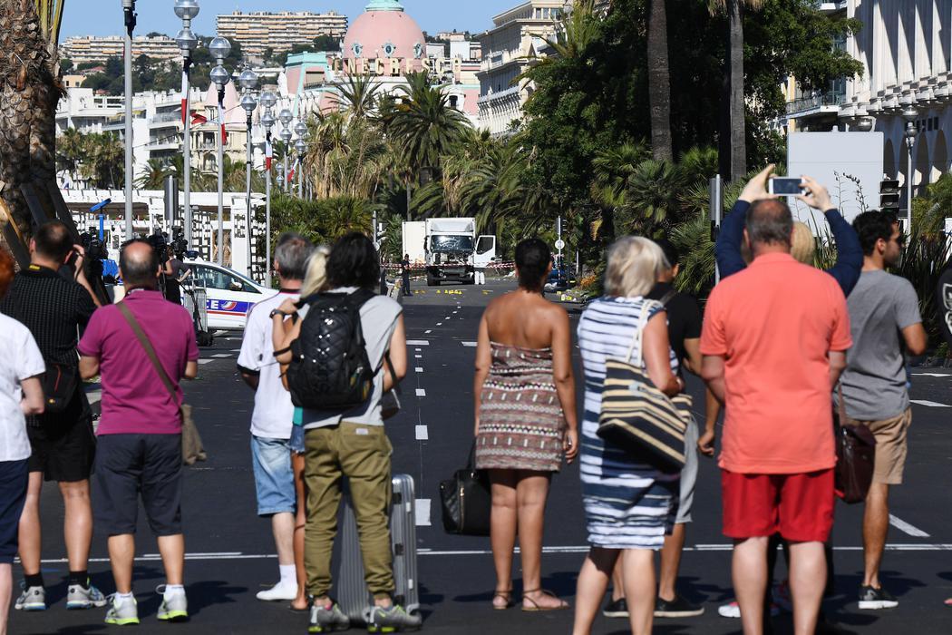Las personas se agolpan para ver a lo lejos del camión del atentado